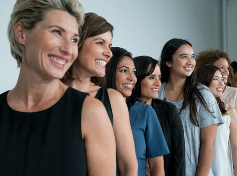 Women in a line smiling for a Cosmetic Dentistry photoshoot at Metropolitan Dental Specialty Group