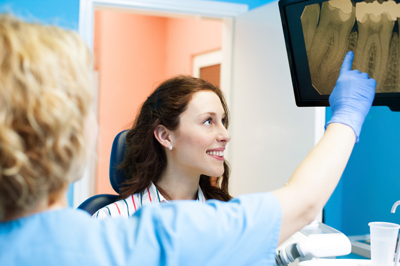 Dentist at Metropolitan Dental Specialty Group revieing digital x-rays with patient