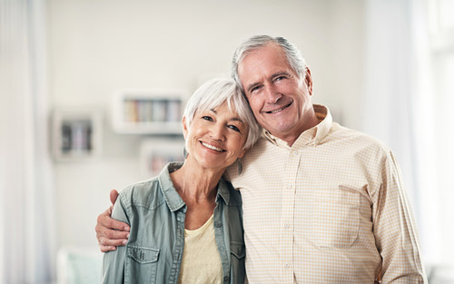 Elderly couple hugging and smiling after recieving oral surgery at Metropolitan Dental Specialty Group